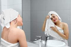 Pretty girl wiping her face with a towel. Picture of pretty girl wiping her face by using a towel while smiling at the mirror. Shot in the bathroom sink Royalty Free Stock Photo