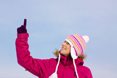 Pretty girl in witer clothes pointing upwards Royalty Free Stock Photo