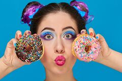 Free Pretty Girl With Her Hair Up Eating A Donuts Stock Photo - 179954190