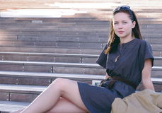 Pretty girl or woman sitting on the stairs Stock Photo