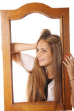 Pretty girl in wooden frame Stock Photography