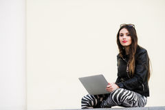 Pretty girl working with laptop sitting on concrete wall outdoors at the university campus Royalty Free Stock Photo