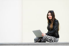 Pretty girl working with laptop sitting on concrete wall outdoors at the university campus Royalty Free Stock Image