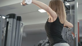 Pretty girl working out in the gym using dumb-bells for muscles and back in 4K stock footage
