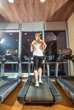 Pretty girl working out in a treadmill at the gym Royalty Free Stock Images