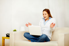 Pretty girl working on sofa with a laptop Royalty Free Stock Photos