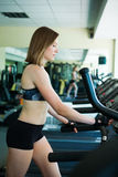 Pretty girl working in treadmill at the gym and smiling Royalty Free Stock Photo