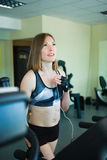Pretty girl working in treadmill at the gym and smiling Stock Images