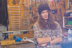 Pretty girl in the workshop with a tool stock image