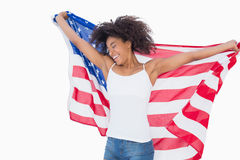 Pretty girl wrapped in american flag cheering. On white background Stock Photos