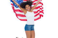Pretty girl wrapped in american flag jumping and smiling at camera Royalty Free Stock Image