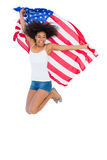Pretty girl wrapped in american flag jumping and smiling at camera Stock Images