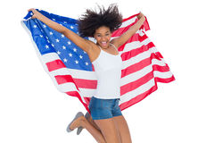 Pretty girl wrapped in american flag jumping and smiling at camera Royalty Free Stock Photography