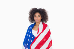 Pretty girl wrapped in american flag looking at camera. On white background Stock Image