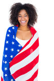 Pretty girl wrapped in american flag smiling at camera Stock Images