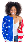 Pretty girl wrapped in american flag smiling at camera Royalty Free Stock Photography