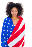 Pretty girl wrapped in american flag smiling at camera Stock Photography