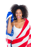 Pretty girl wrapped in american flag smiling at camera Stock Photos