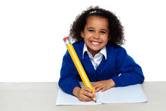 Pretty girl writing in her notebook. And flashing smile by grinding her teeth Stock Photo
