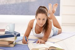 Pretty girl writing homework laying on floor Stock Images