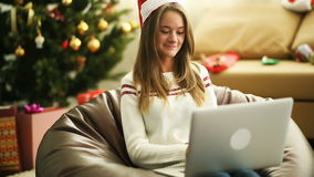 Pretty girl writing letter to Santa Claus on laptop at Christmas eve. Close up of young pretty girl in red Christmas cap using laptop. Blur christmas tree at stock footage