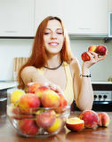 Pretty girl in yellow eats peaches Stock Image