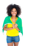 Pretty girl in yellow tshirt and brazilian flag smiling at camera Stock Images