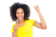 Pretty girl in yellow tshirt and denim hot pants cheering at camera Royalty Free Stock Photography