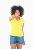 Pretty girl in yellow tshirt and denim hot pants pointing at camera Stock Images