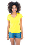 Pretty girl in yellow tshirt and denim hot pants smiling at camera Stock Photos