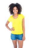 Pretty girl in yellow tshirt and denim hot pants smiling at camera Royalty Free Stock Photo