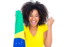Pretty girl in yellow tshirt holding brazilian flag cheering at camera Stock Photography