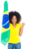 Pretty girl in yellow tshirt holding brazilian flag cheering at camera Royalty Free Stock Photography