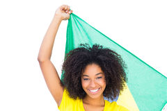 Pretty girl in yellow tshirt holding brazilian flag smiling at camera Royalty Free Stock Images