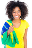 Pretty girl in yellow tshirt holding brazilian flag smiling at camera Stock Image