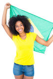 Pretty girl in yellow tshirt holding brazilian flag smiling at camera Stock Photos