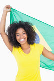Pretty girl in yellow tshirt holding brazilian flag smiling at camera Royalty Free Stock Photography