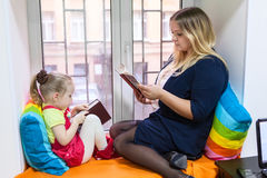 Pretty girl with young mother read books on window sill stock photo