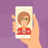 Pretty girl young woman takes selfie using a smartphone. Royalty Free Stock Photography
