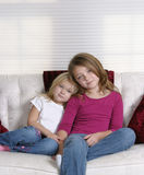 Pretty Girls. Pretty blonde and brunette young girls sitting on white couch Stock Images