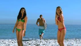 Pretty girls admiring a friend running toward the sea