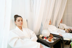 Pretty girls in bathrobes relaxing in armchairs Stock Images