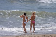 Pretty girls at the beach. Two young pretty girls stand on the beach watching waves stock photography
