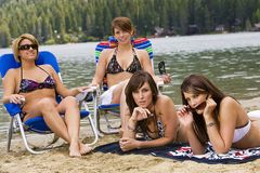Pretty Girls at the Beach. Four Pretty Girls wearing bikinis at the lake getting a sun tan Royalty Free Stock Photo