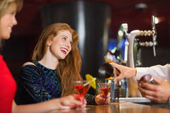 Pretty girls being served cocktails Stock Photography