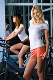 Pretty girls on bicycle simulators Royalty Free Stock Image