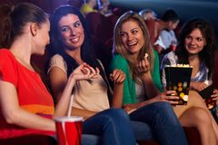 Pretty girls in cinema talking smiling. Pretty young girls sitting in auditorium of cinema, talking, smiling, eating popcorn Stock Photography