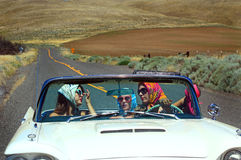Pretty Girls in Convertible. Three attractive pretty girls riding in a convertible with the top down out on a desolate country road. Shallow depth of field Royalty Free Stock Image