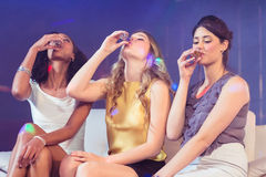 Pretty girls drinking alcohol. In a nightclub Stock Photography