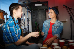 Pretty Girls Drinking Beer in  Night Club Party. Portrait of two beautiful  girls clinking beer bottles at night club party Stock Photo